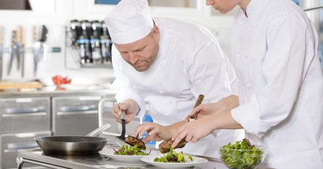 Two chefs prepare meat dish in a professional kitchen at restaurant or hotel.